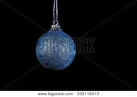Close-up Shot Of Glistening Azure Ball On Black Background, Christmas And New Year Decoration On Dar