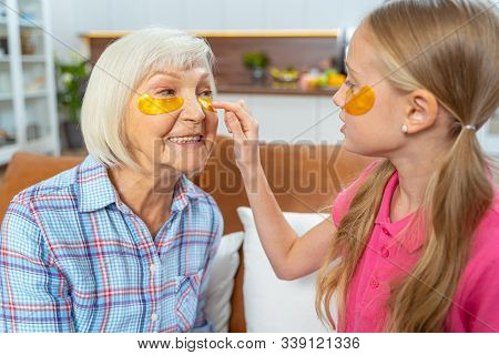 Serious Grandchild Taking Care Of Her Grandmother