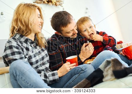 Christmas Family. Dad, Mom And Son Spending Time Together, Eating Cookies And Drinking Cocoa In The