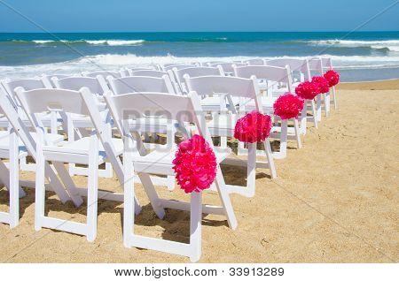 White wedding chairs on the beach
