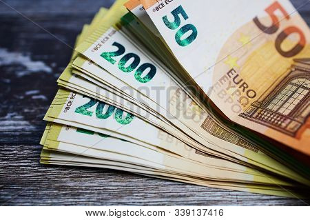 Stack Of Fity, Hundred And Two Hundred Euro Banknotes Against Wooden Surface