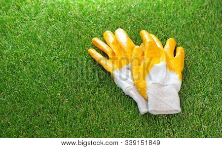 Protective Gloves Lie On The Artificial Grass Lawn