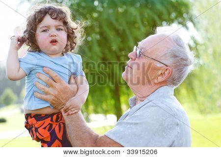 Happy granddad holding his grandson in hands