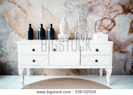 A New White Dresser Against The Backdrop Of An Abstract Wall. Buddhas Head Next To Vases On The Dres