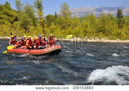 Rafting, A Group Of Young People With A Guide Rafting Along A Mountain River. Extreme And Fun Sport