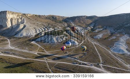 Balloons Soar Over The Valley Amid Protruding Mountain Ranges, The Morning Sun Draws Long Shadows Cr
