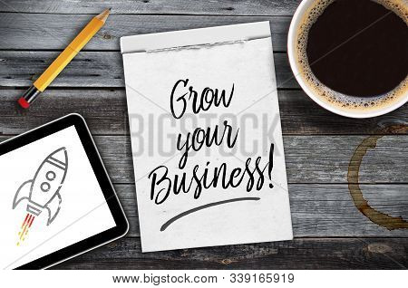 Sketchbook With Written Message Grow Your Business On A Wooden Desk With Tablet, Pencil And Cup Of C