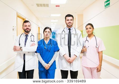 Hispanic Male And Female Healthcare Workers Standing In Corridor At Hospital