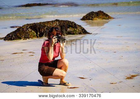 Tourist Woman Relaxing Walking On Sea Shore With Camera, Taking Travel Photos. Coast Of Gimsoya Isla