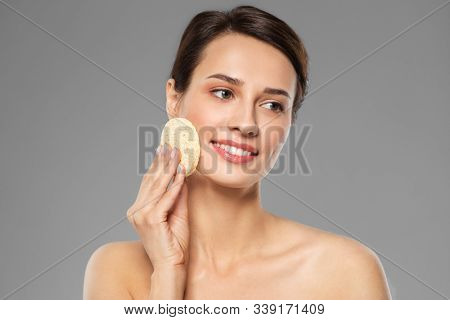 beauty, people and skincare concept - young woman cleaning face with exfoliating sponge over grey background