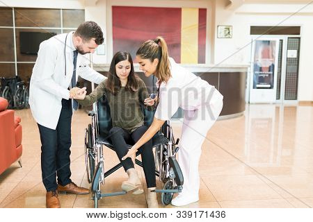 Male And Female Latin Doctors Assisting Young Woman To Stand Up From Wheelchair Before Leaving From