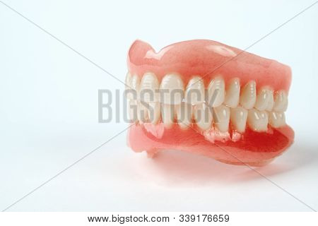 Diagnosis Prosthetics Treatment Concept. Artificial Teeth And Magnifying Glass