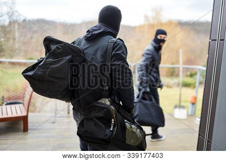 Two burglars flee from a house with bags full of loot