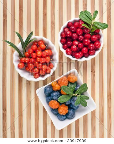 fresh wild berries in bowls on a wooden surface striped table
