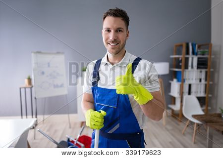 Full Length Portrait Of Happy Male Worker With Broom Cleaning Office