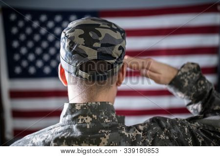 Portrait Of Serious Solider Standing In Front Of Us Flag Saluting