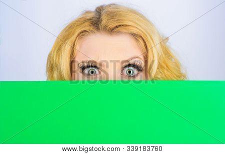 Surprised Woman With Blank Billboard. Blond Girl Peeking From Behind Blank Sign. Woman Hiding Behind