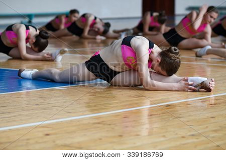 Athlete Warming Up Before Training Sitting On The Floor, Horizontal Twine, Woman Holds Her Foot And