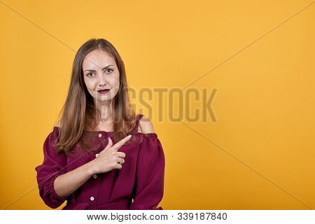 Girl In Burgundy Bluse Over Isolated Orange Background Undecided Pointing Finger To Right With Doubt