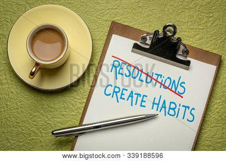 create habits instead of resolutions  - handwriting on a clipboard with a cup of coffee, New Year goals, resolutions and personal development concept