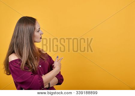 Girl In Burgundy Bluse Over Isolated Orange Background Undecided Pointing Finger With Doubts Looking