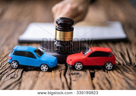 Two Cars In Front Of Gavel And Mallet And Judge Striking The Mallet