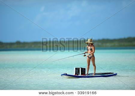 Woman In Bikini Fishing And Paddle Boarding