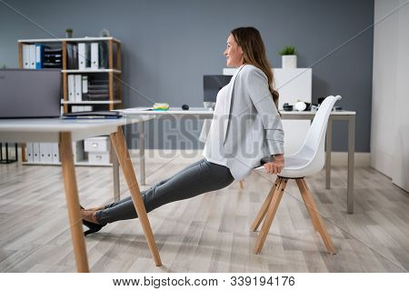 Side View Of A Young Businesswoman Doing Triceps Dips In Office