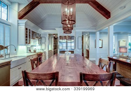 Large luxury kitchen with wood table and high end appliances.