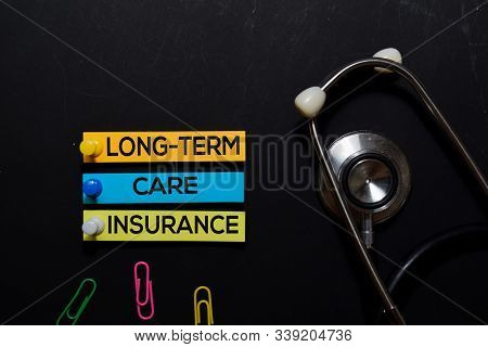 Long-term Care Insurance Text On Sticky Notes. Top View Isolated On Black Background. Healthcare/med