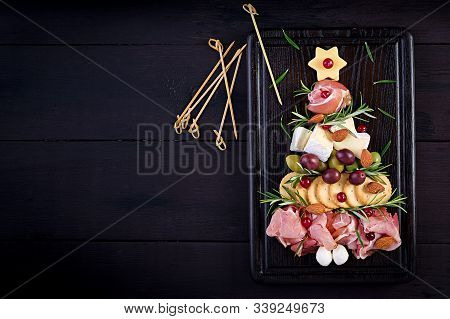 Antipasto Platter With Ham, Prosciutto, Salami, Cheese,  Crackers And Olives On A Wooden Background.