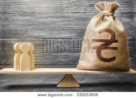 Ukrainian Hryvnia Uah Symbol On Money Bag And People On Scales. Concept Attracting Investment, Busin