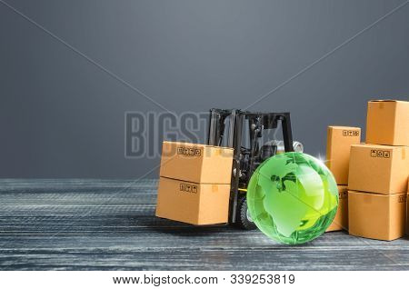 Green Glass Globe And Forklift Truck With Cardboard Boxes. Distribution And Trade Exchange Goods Aro