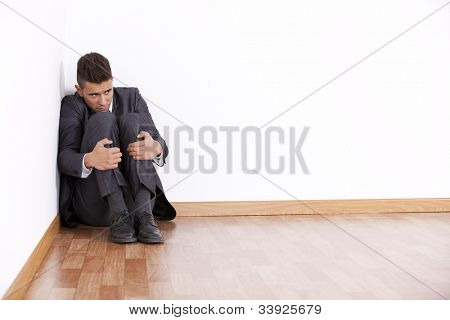 Businessman at the corner of his office room with fear