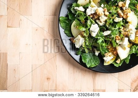Salad Of Pear, Blue Cheese, Arugula And Nuts With Spicy Dressing On A Wooden Background. Healthy Eat