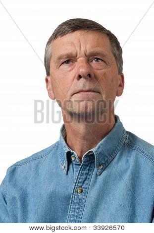 Senior Man In Blue Shirt Looks Pensive