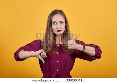 Young Woman Over Isolated Orange Background Making Good-bad Sign. Undecided Between Yes Or Not. She