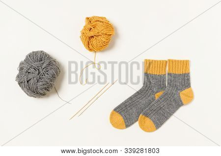 Two-toned Socks, Yellow And Grey Clews Of Wool Yarn And Wooden Bamboo Knitting Needles. Flat Lay. Cr
