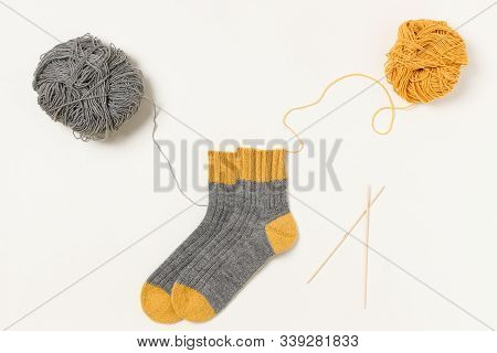 Two-toned Socks, Yellow And Grey Clews Of Yarn And Wooden Bamboo Knitting Needles. Threads From The
