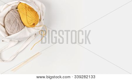 Yellow And Beige Clews Of Yarn In A Textile Bag. From The Yellow Skein Of Yarn A Thread Runs To The
