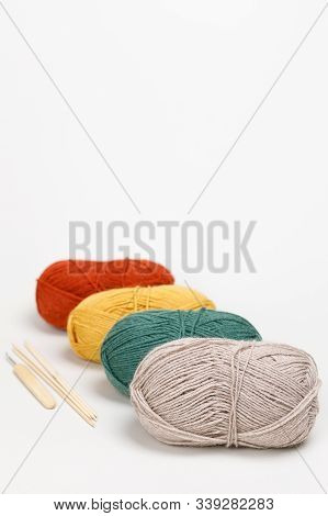 Beige, Green, Yellow And Red Clews Of Yarn Of Pastel Colors Lie One Behind The Other. Nearby Is Hook