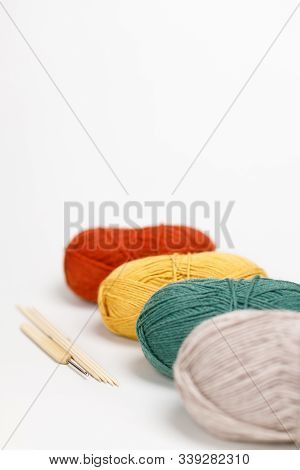 Beige, Green, Yellow And Red Clews Of Yarn Lie One Behind The Other. Nearby Is Hook And Wooden Knitt