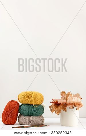 Vertical Photo Of Red, Green, Yellow And Beige Clews Of Yarn Of Pastel Colors And Multicolored Woode
