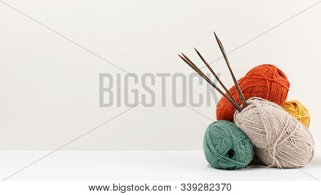 Red, Green, Yellow And Beige Pastel Colored Clews Of Yarn. Multicolored Wooden Knitting Needles Stuc