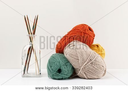 Multicolored Bamboo Wooden Knitting Needles In Glass Jar And Red, Green, Yellow And Beige Pastel Col