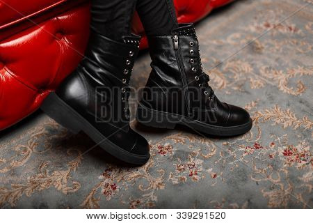 Close Up Of Female Legs In Trendy Jeans In Seasonal Stylish Leather Black Lace-up Boots In The Room.