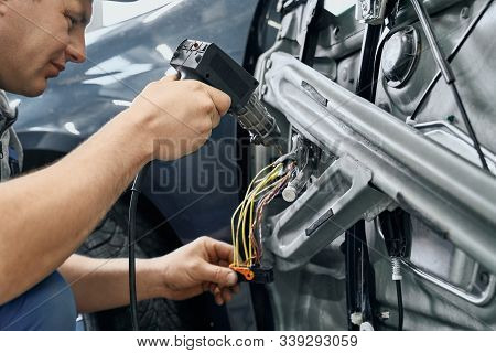 Side View Of Car Electric Repairman Holding And Using The Soldering Iron To Blend The Wires For Repa
