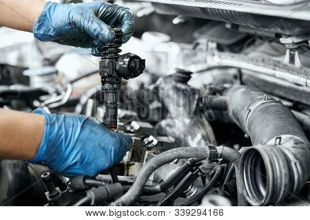 Male Specialists Hands In Dusty Rubber Gloves Holding New Nozzle For Car Engine In Service Station.