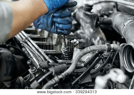 Close Up Of Mans Hands In Dusty Rubber Gloves Keeping Screwdriver And Tighten Bolts In Spark Plugs F