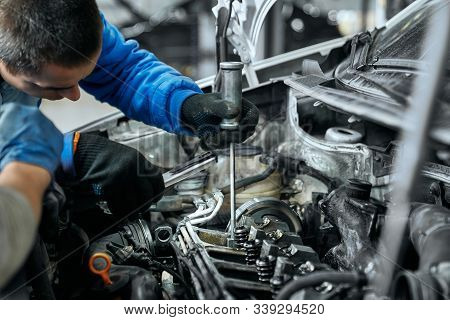 Auto Mechanic In Blue Uniform And Black Gloves Replacing Glow Plugs In Car Diesel Engine Using Spark